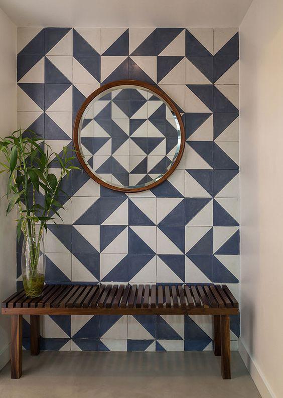 Hall com parede em ladrilho hidráulico azul e branco, espelho redondo com moldura em madeira e banco ripado em madeira. #bancomadeira #espelhoredondo #hall #decoracao